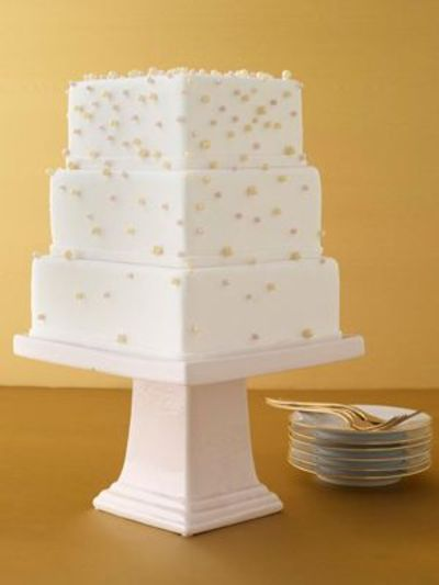 Gradually varying amounts of pearl decorations on square three-tier cake