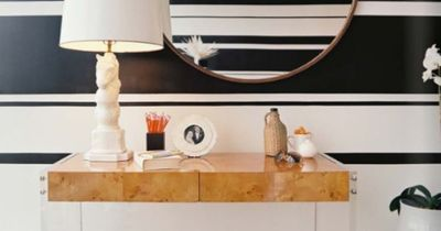 black and white stripes, large round mirror, burled wood and lucite table, and ceramic horse lamp.