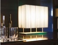 Makassar contemporary Italian table lamp shown in white fabric. Table lamp in satin-finish steel strucutre. Lamp shade in pliss fabric. Available in ivory, black or