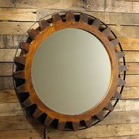 Wooden Gear Mirror A solid wood carved gear is strapped with a black iron strap for a rustic look that can also go industrial. Use in a modern loft setting or a rustic lodge. Perfect size for a bath or powder room.