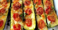 Slice the zucchini in half. Slice off the bottom to keep in stable. Brush with olive oil and top with garlic or garlic powder. Top with sliced tomatoes, salt and pepper to taste. Use mozzarella cheese, Parmesan cheese or mixed blend.. Bake 375 for 20 to 3...