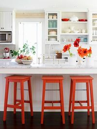 White kitchen with light countertops an a pop of color.