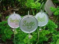 Make your own garden markers with wire hangers, juice can lids, and beads. Cute!