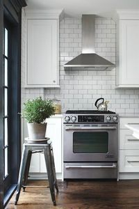 stainless steel range hood with white subway tile backsplash