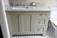 Beautiful gray green bathroom design with gray green bathroom cabinets, white carrara marble counter top, polished nickel hardware, white & black floors and polished nickel faucet.