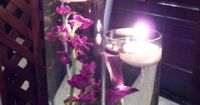 Purple flowers in water with floating candles
