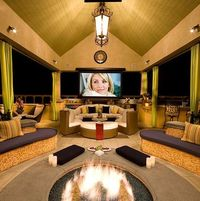 Outdoor media room. Big TV, fire pit, couches, and a bar, I'm in love. Only thing missing is the hot tub