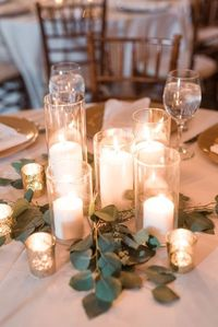 Courtney Inghram Events floral design photographed by Audrey Rose Photography at Early Mountain Vineyards in Virginia. Romantic candlelit pillar candle centerpiece with eucalyptus greenery and gold mercury glass votives for a winery wedding. Organic weddi...