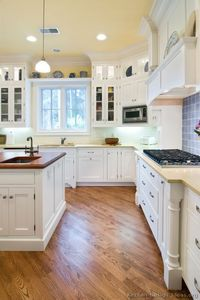 A lovely cottage kitchen with white cabinets, wood floors, and a beautiful wood hood... #3 in Traditional White Kitchen Cabinets *I'd prefer non-white, but the layout & floors are nice.