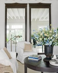 Love this room: white furniture; floor-to-ceiling mirrors in dark wood (mahogany?); beamed ceiling; dark round Swedish table w/urn and wild flowers