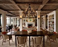 open concept home - natural wood ceiling + bookshelves + wood floors + fireplace + candle chandelier