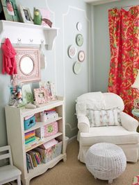 Soft teal walls create a great contrast against the curtains made from bright coral fabric for a color palette that's not typical for a little girl's room.