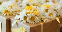 Gift wrapping idea | faux or fresh flowers to decorate the top of a gift wrapped box.