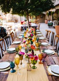Combine bright beautiful blooms, Mexican serape style linens, and colorful glassware and you get an elegant Mexican Fiesta wedding like this - just what designe