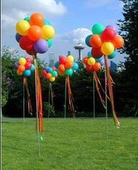 Balloon topiaries. cheap and easy to do, big impact. Outside the main doors during the week?