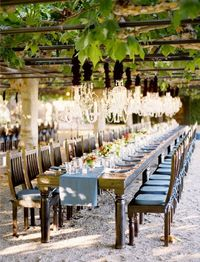 Love this long #rustic table with #chandeliers hung from the patio.