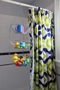 metal hanging fruit basket over the shower curtain rod to hold toys