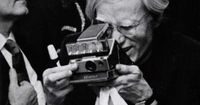 Andy Warhol and his Polaroid camera. Taken at Jimmy's Disco by notorious paparazzo Ron Galella in 1973.