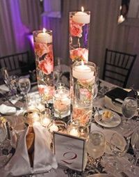 Tall floating candle centerpieces with flowers