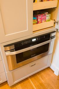 Microwave drawer beneath full-height pantry with roll-out shelves