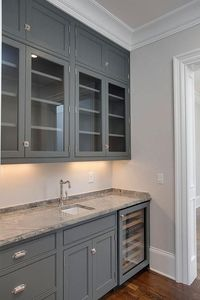 Grey butler pantry features glass front upper cabinets and gray lower cabinets fitted with a glass ...