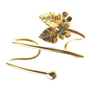 Delicate and very feminine gold plated leaves and flowers mingle with bright turquoise forming an exquisite handcrafted bracelet.