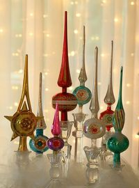 Vintage tree toppers displayed in glass candle holders.