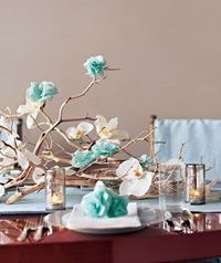 I love this table setting. Real flowers mixed with tissue paper flowers and pretty candles.