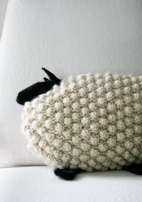 A pattern to make your own knitted bobble sheep pillow.