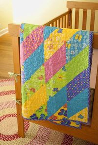 Brightly colored half-squared triangles produces vibrant diamonds in a quickly pieced baby quilt.