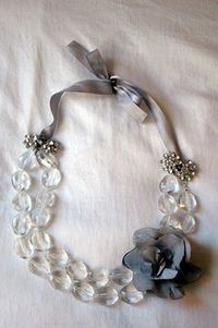 DIY - Fold a necklace in half. Attach ribbon to both ends. Add embellishment to hide the ribbon knots. Add flower pin.