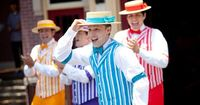 A group of 4 men sing and perform outside wearing boater hats, arm garters and striped vests #Disneyland