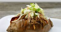 Rich, tangy BBQ beef piled atop a baked sweet potato and topped with creamy coleslaw. It's all here in this Smothered BBQ Sweet Potato with Slaw recipe.