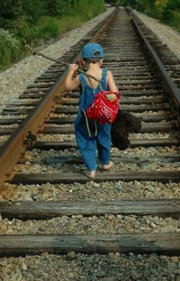 little runaway...coveralls, a bandana bag and a stuffed bear are the perfect props for a photo on the train tracks