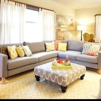 Light and bright living room. Neutral furniture, pops of color, bold print on the ottoman.