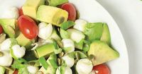 Healthy Avocado Caprese Salad full of rich dietary fats and Omega-3's. Fresh mozzarella, avocado, cherry tomatoes, cucumber, olive oil and pumpkin seeds.