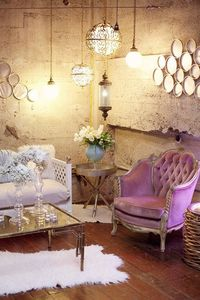 With concrete walls it's difficult to warm up a room. The designer does this with multiple hanging pendents, mirrors to bounce the light across the angles of the room, soft rugs for the floor, and plush seating with pillows to make an inviting space t...