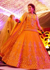 This beautiful Mehndi dress has a net shirt with gotta work all over. The net lehnga with aesthetically embellished panels is accompanied by a net dupatta. The dupatta is created with a motives spray and arches on the sides.