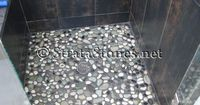 Similar with the dark wall tiles and pebble flooring in the shower