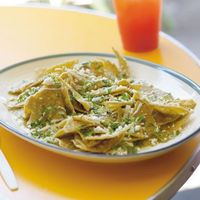 Chilaquiles Verdes are a traditional Mexican peasant dish of fried tortillas bathed in green or red salsa (depending on the region) until tender. Slightly tart green tomatillo sauce is preferred in Mexico City, and is very simple to make. Chilaqui...