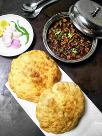 Chole bhature is a popular Indian breakfast made with chickpeas curry and puffy fried bread called bhature made from refined flour.