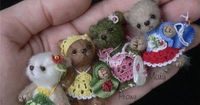 Needle felted tiny bears in crocheted dresses.