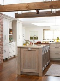 Exposed brick, white cabinets, and different coloured kitchen island