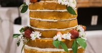 A three-tier naked cake was garnished with fresh strawberries and flowers. Venue: The Warehouse at Alley Station Floral Designer: Southern Posies Cake: Peggy Mc