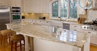 White cabinets and white countertops with subtle gold veining - very clean design. The granite is Colonial Gold and it matches the warm and bright design of this kitchen.