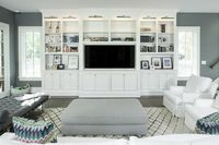 White and charcoal gray living room features a pair of white slipcovered chairs facing a gray ottoman atop a beni ourain rug facing a white built-in tv cabinet illuminated by nickel picture lights.