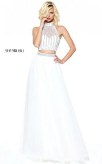 Make an appearance at your social event in this exquisite dress from Sherri Hill. Style 50786 showcases a halter neckline embellished with silver stones to form a vertical stripe pattern along the crop top for a glitz and glam look. The beaded belt cinche...