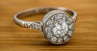 Stunning Vintage Style Diamond Engagement Ring set with a lively old mine cut diamond in the center. It's surrounded by a halo of smaller diamonds.